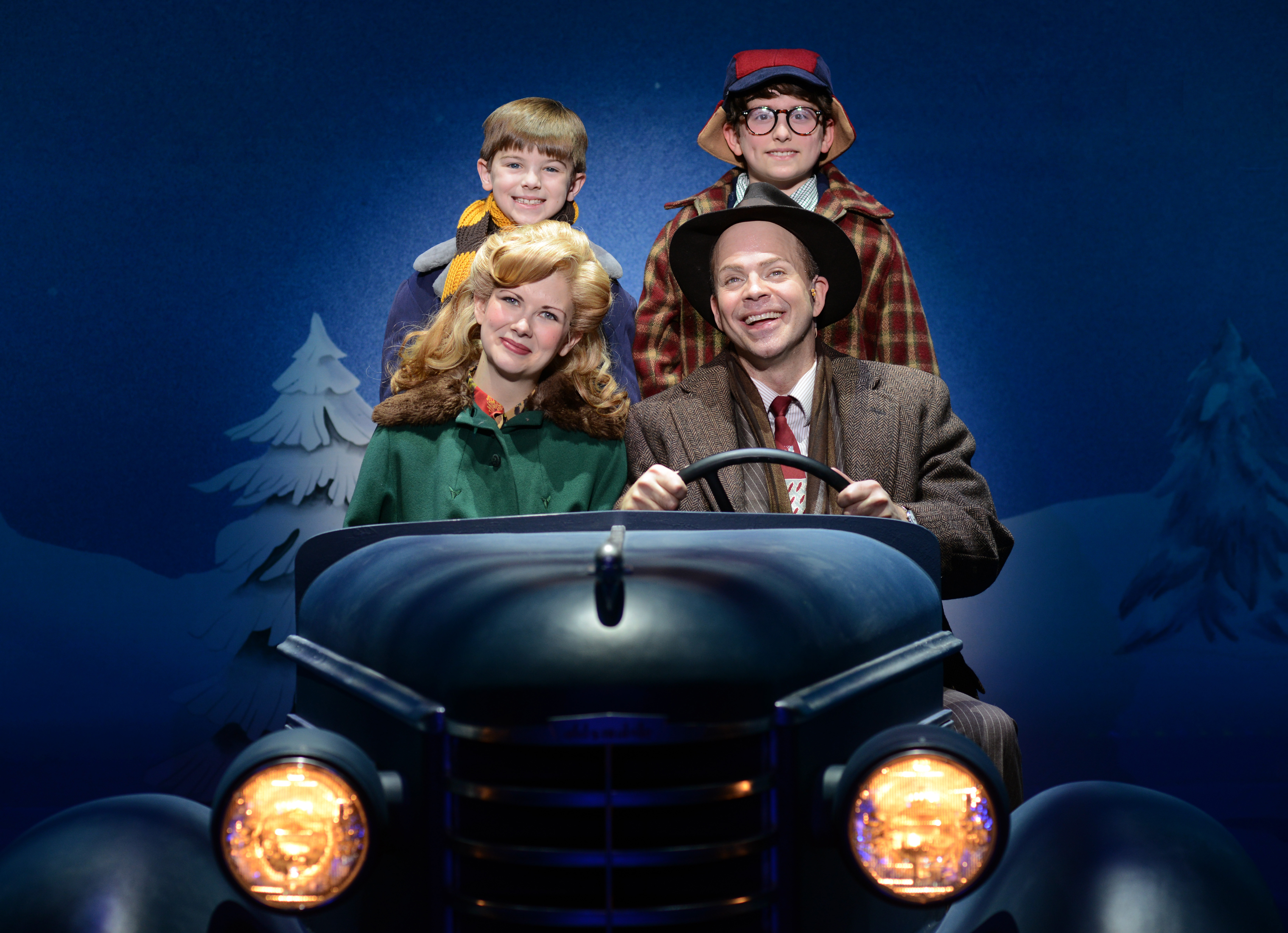 The Parker family sits in their car. We see the bottom portion of the car with headlights, while the windshield and top of car are removed for visibility. Father sits at the steering wheel with mother beside him in the front passenger seat and the two sons behind in the back seat. They are dressed for winter: various jackets, scarves, and hats. Behind them is a winter scene, pine trees stand on an outline of snow covered hills.